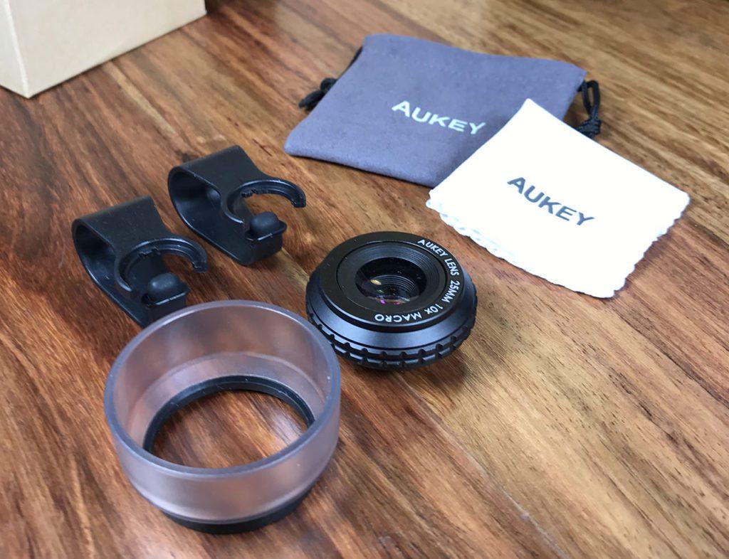 Im Lieferumfang: Das Aukey Aufsteckobjektiv, eine Hülse, zwei Ansteckclips, ein Beutelchen und ein Mikrofasertuch für die Reinigung.