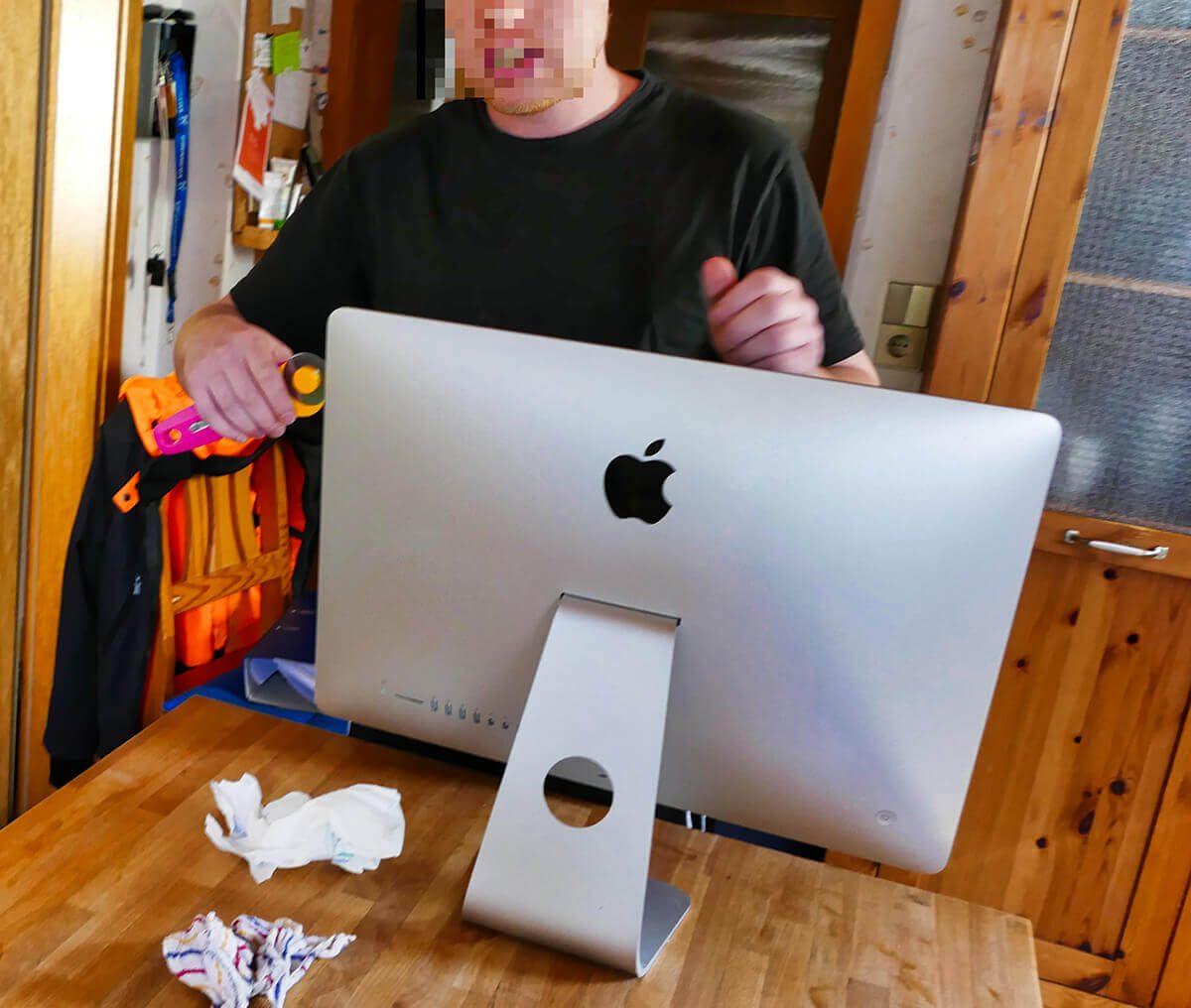 Das Bild zeigt Jürgens Sohn, wie er mit Hilfe des Rollmessers den iMac aufschneidet. Durch die Schnitte werden die Verklebungen getrennt, die das Display mit dem Rest des iMacs verbinden.