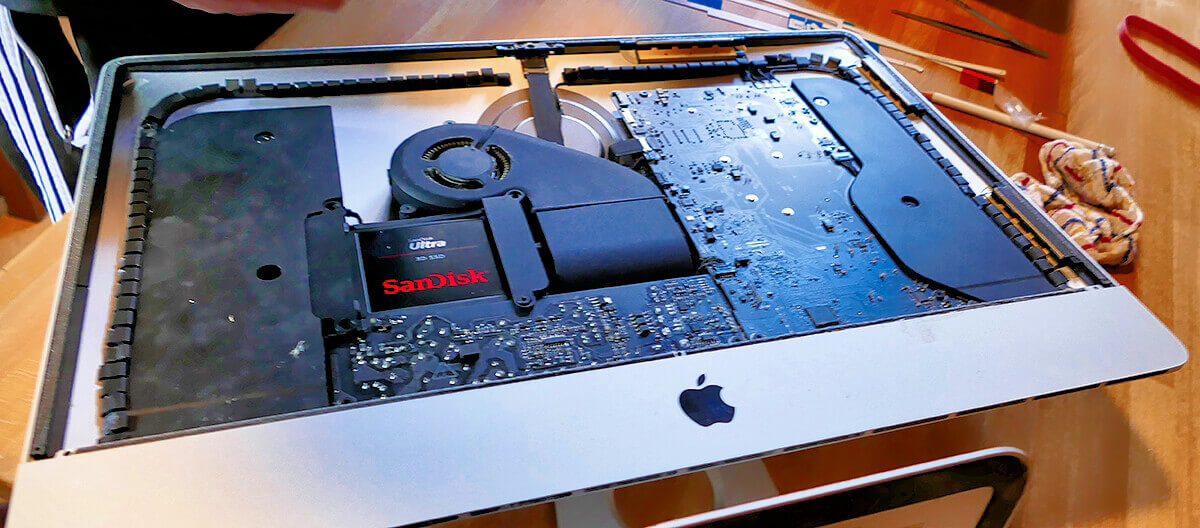 Der geöffnete iMac mit Apple-Logo und bereits verbauter SanDisk SSD.
