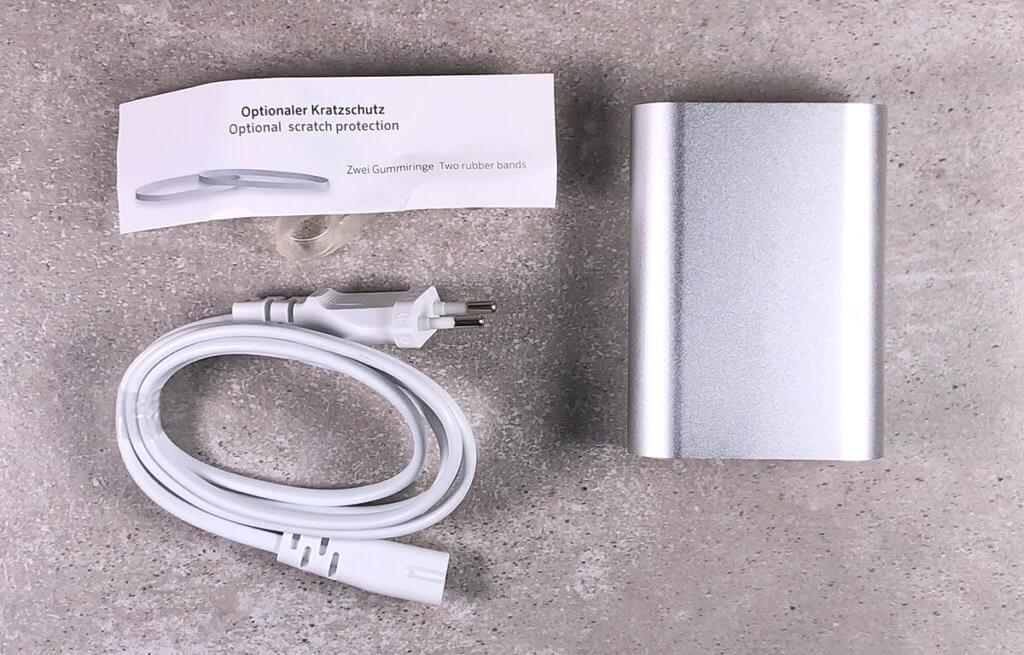 Im Lieferumfang des USB-C Netzteils von Artwizz sind neben dem Ladekabel auch zwei Gummibänder enthalten, die das Gehäuse vor Kratzern schützen sollen. Eine entsprechende Anleitung zur Verwendung liegt bei.
