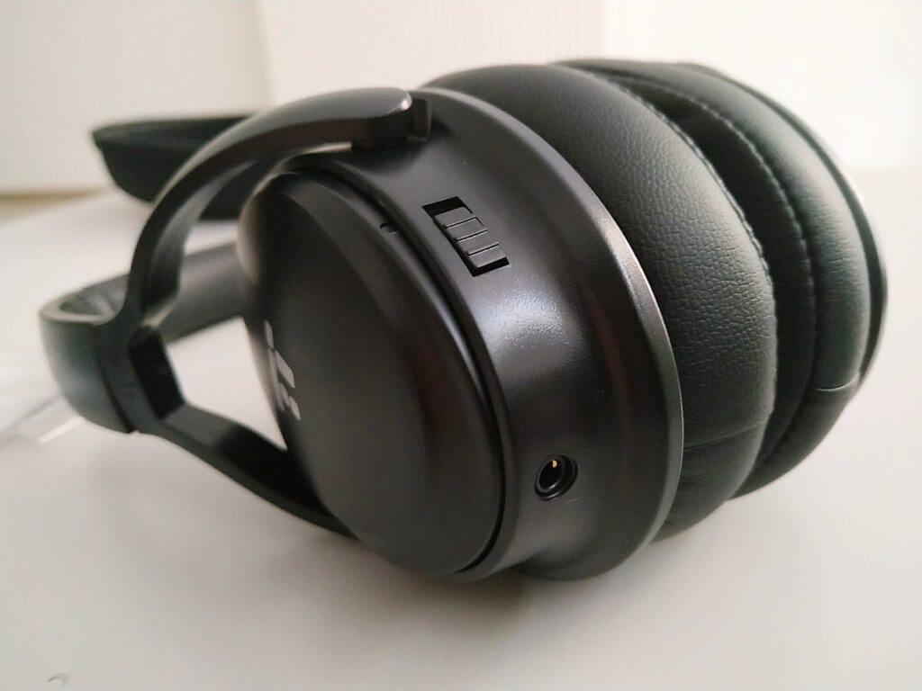 Mit dem Schalter lässt sich das Active Noise Cancelling zuschalten. Darunter befindet sich die Klinkenbuchse für die Verwendung als kabelgebundene Kopfhörer.