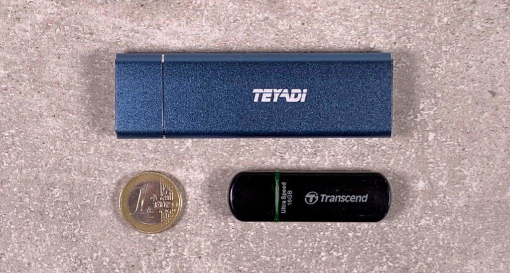Um die Größe der SSD mal im Verhältnis zu sehen, habe ich sie hier mit einem Euro-Stück und einem üblichen USB-Stick abgelichtet.