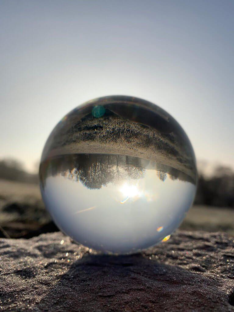 Zerbrechlich wirkende Glaskugel auf gefrostetem Stein – manchmal passt alles…