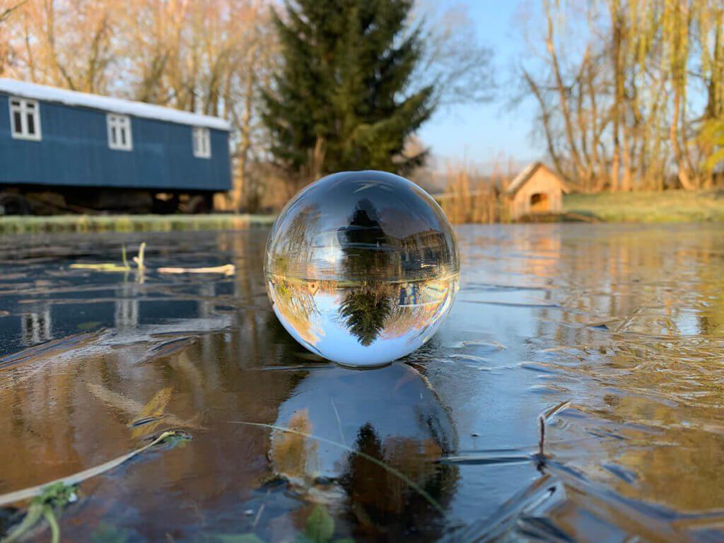 Lensball auf gefrorenem Teich – sieht nicht nur schön aus, sondern ist auch lustig: Wenn man die Kugel dreht, hört sie nicht mehr auf, sich zu drehen, weil die Reibung zwischen Eis und Glas so gering ist.