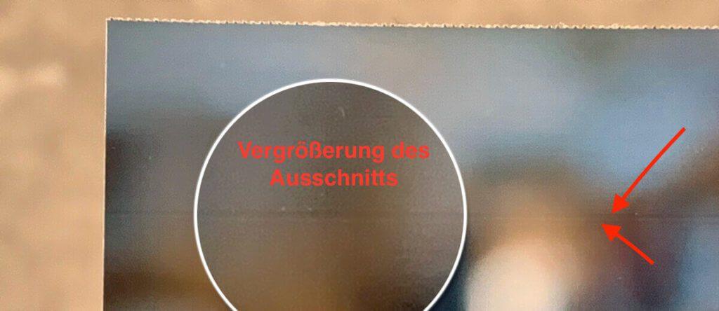 Hier sieht man – durch die Pfeile und die Vergrößerung deutlich gemacht – die dunkle Linie, die oben durch das Foto verläuft.