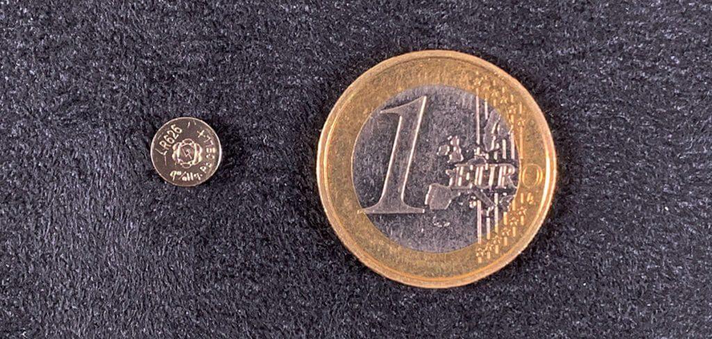 Im Größenvergleich mit dem 1-Euro-Stück sieht man erst, wie klein die SR626SW Batterie tatsächlich ist (Foto: Sir Apfelot).