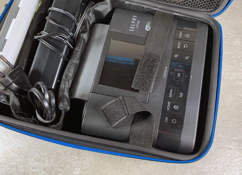 Auf diesem Foto sieht man das flexible Sicherungsband, das man mit Hilfe von einem Klettverschluß schließen kann, um den Drucker vor ungewollten Bewegungen zu schützen.