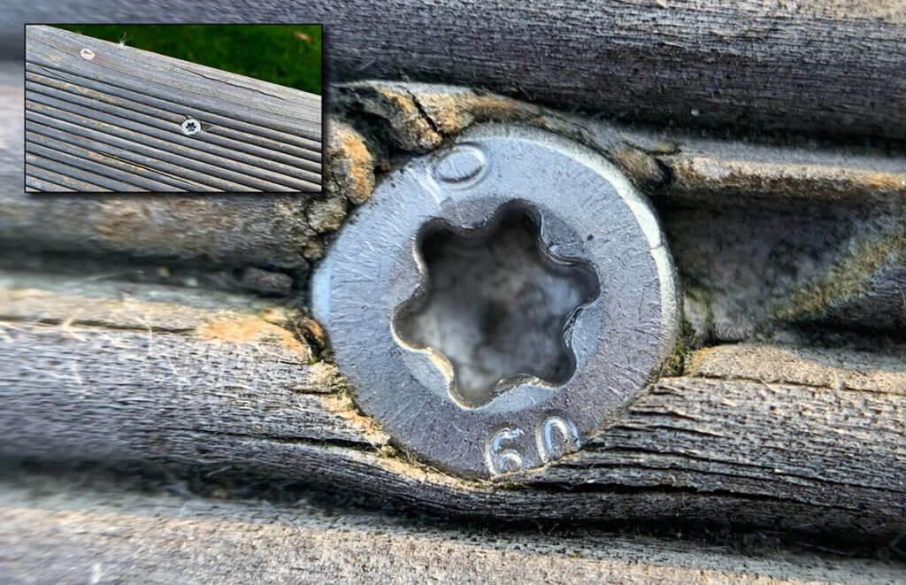 Ein Torx-Schraubenkopf auf einer Terrassendiele. Oben links sieht man ein normales Foto der Diele.