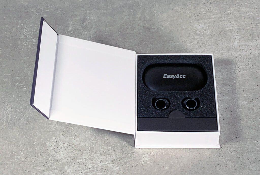 Auch im Inneren der Packung sieht es aufgeräumt aus. Das Zubehör wie Ladekabel und Silikonstöpsel sind unter dem Schaumstoff bzw. in einem dunklen Karton am Rand untergebracht.