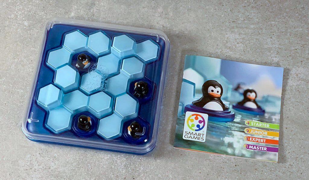 Die Spielfiguren, Eisberge und Anleitung passen auf das Spielbrett und können mit einem Deckel verschlossen werden – perfekt zum Verstauen und mitnehmen.