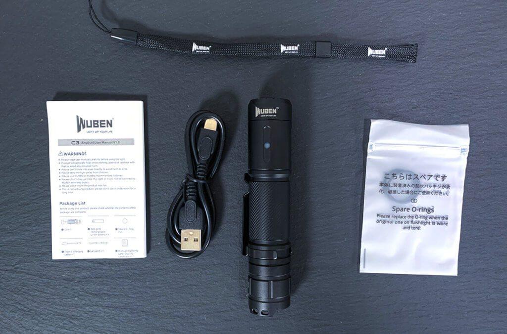 Hier sieht man den Lieferumfang der LED Taschenlampe von Wuben: rechts im Bild ist das Tütchen mit den zwei O-Ringen.