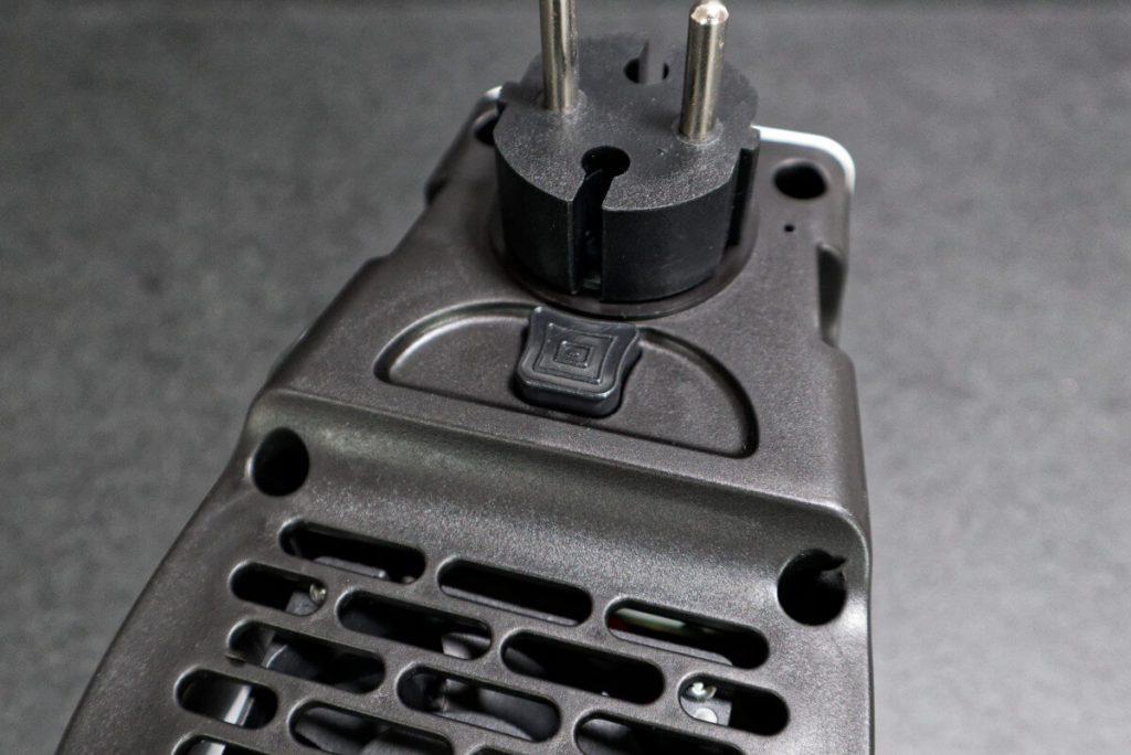 Auf der Rückseite findet man den Taster, der die Ausrichtung des Steckers entsperrt. Weiter unten ist das Lüftungsgitter, über die der Ventilator die Luft ansaugt.