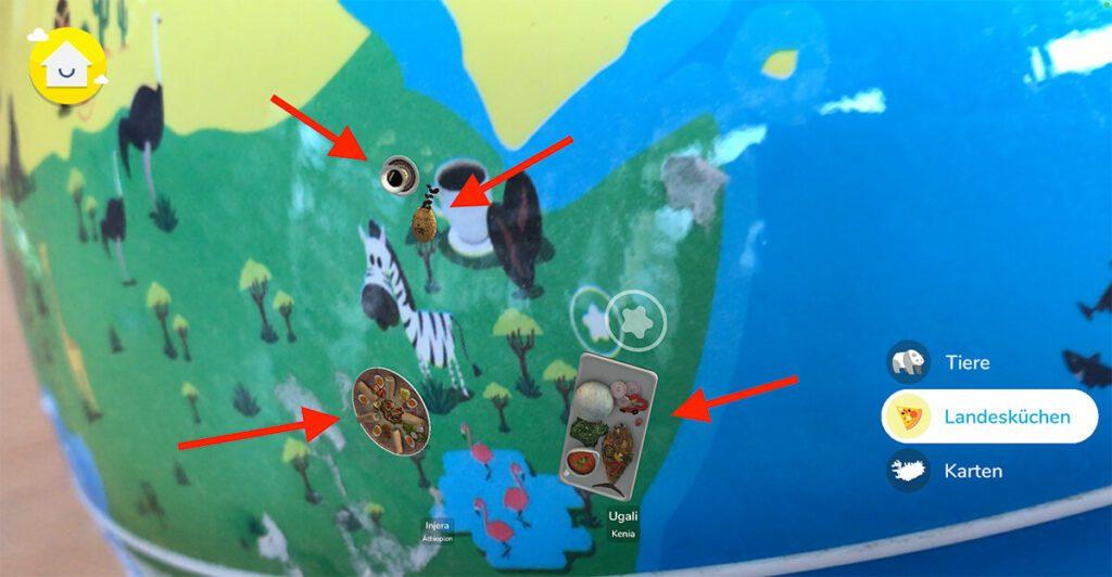 """Wählt man den Layer """"Landesküchen"""" in der AR-App zum Erkunden aus, kann man sehen, welche Nationalgerichte es in den verschiedenen Ländern der Erde gibt. Ein Tipp darauf, bringt dann weitere Informationen zu dem Gericht und dessen Herstellung. Ich habe die roten Pfeile im Bild eingebaut, damit ihr seht, welche Objekte per AR hinzugefügt wurden (Fotos: Sir Apfelot)."""