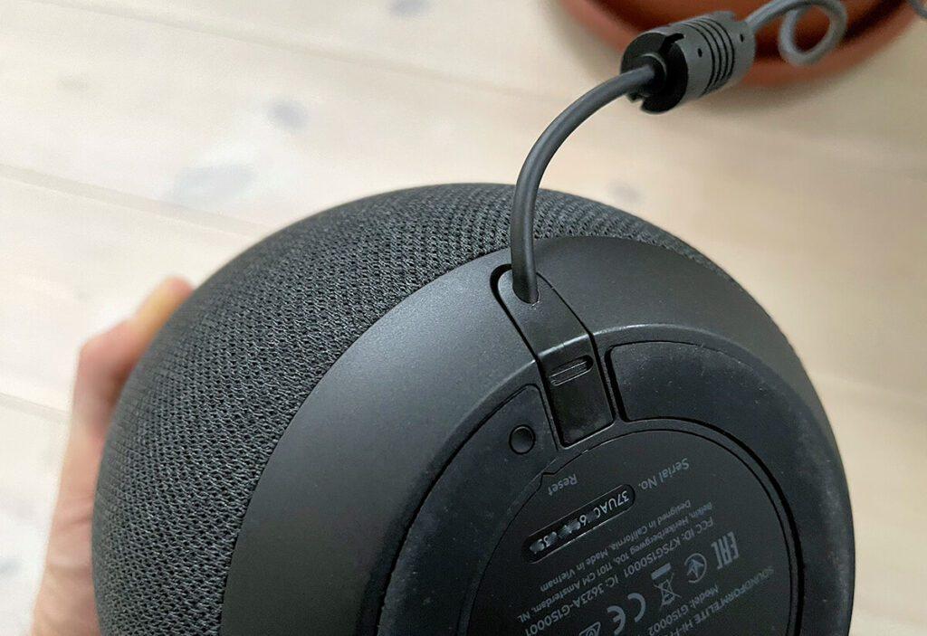 Auf der Unterseite befindet sich der Reset-Knopf zum Zurücksetzen. Ebenso sieht man schön, wie gut sich das Stromkabel in die Form des Lautsprechers einfügt.